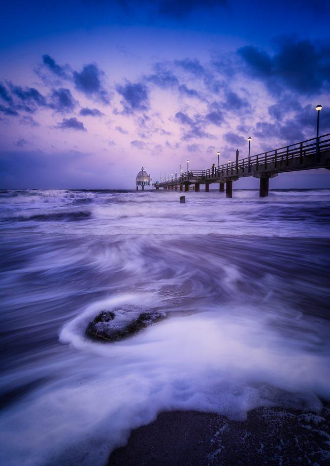 Die Seebrücke in Zingst bei stürmischer Ostsee zum Sonnenaufgang